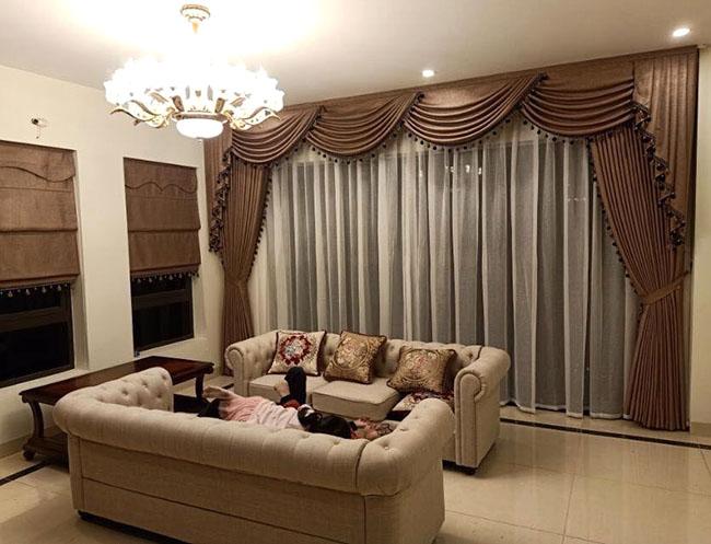 Bộ sofa êm ái màu ghi sáng được tôn vinh nhờ thiết kế rèm vải cầu kỳ