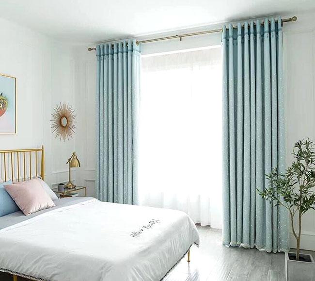 Không gian phòng ngủ màu trắng kết hợp bộ rèm xanh nước biển tạo sự trẻ trung