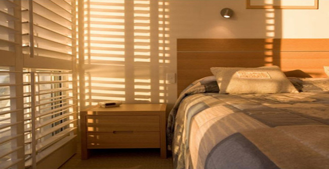 Chiếc rèm gỗ màu trắng tạo cảm giác rộng rãi cho phòng ngủ