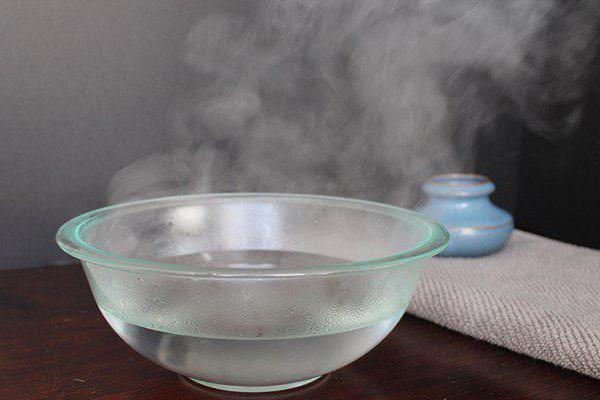 Giót nước nóng ra một chiếc bát để ngâm vết kẹo cao su