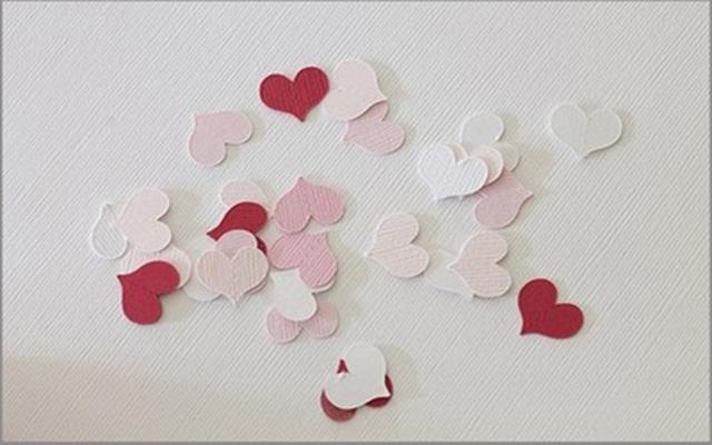 Hình trái tim bằng giấy được cắt đều trước khi tạo lên rèm cửa sổ